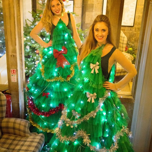 Human Christmas Trees stilt walkers for light switch on