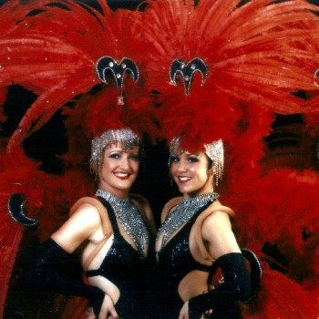 Show Girls in black costumes with red feather head dresses