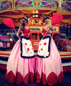 Stilt Walker in Queen of hearts Alice in Wonderland theme costumes at funfair
