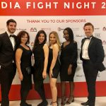 Event hosts and hostesses in front of sponsor board for Media Fight Night 2018