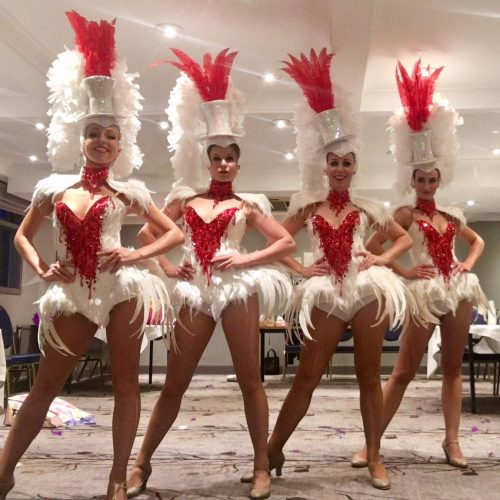 Showgirls pose in red and white feathered costumes