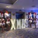 Showgirls pose with large XMAS LED sign